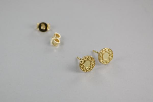 graphischer Ohrstecker, flaches gelbgoldens Ornament auf einem kleinen Ohrstecker