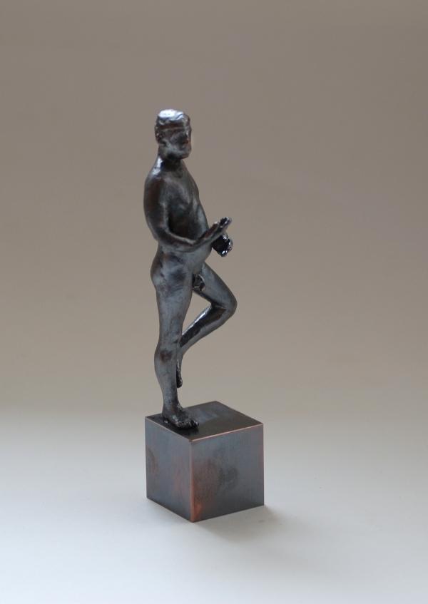 kleine, nackte, männliche Bronzepalstik auf einem Bein stehend, dss andereabgewinkelt und bis zum Knie nach oben gezogen von David dott