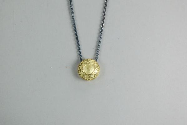 Gelbgoldanhänger mit dem Ornament des Brillant als Relief in Kontrast zur geschwärtzen Kette