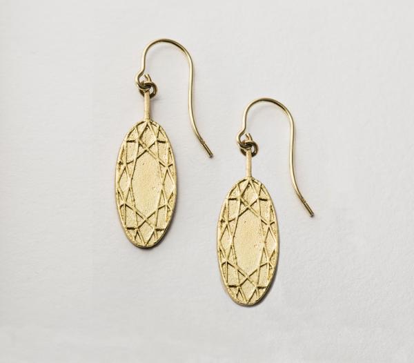 ovale ohrhänger aus 18ct gold, auf dem flachen Schmuck ist ein symmetrisches Ornment abgebildet