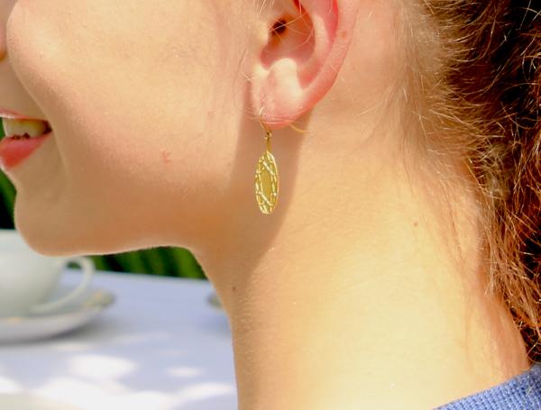 ovale Ohrhänger aus gold mit symmetrischem Ornament am Ohr getragen