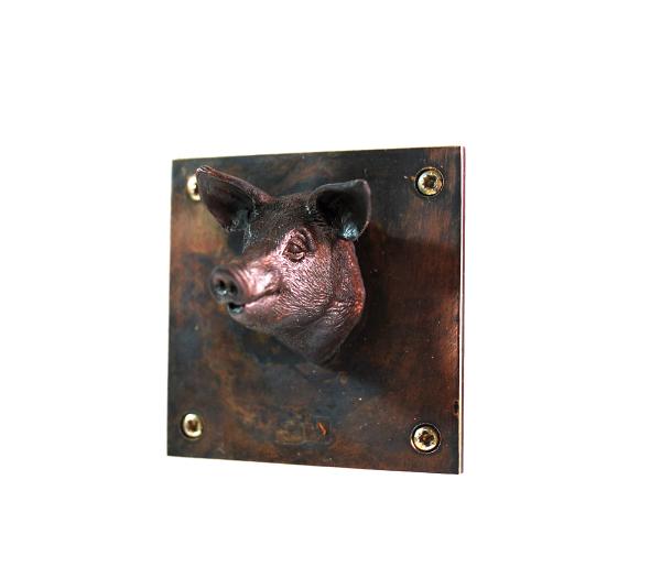 Kleinskulptur Schwein aus Bronze, auf 5 x 5 cm großer Platte sitzt der Schweinkopf mittig und sieht einen frech an