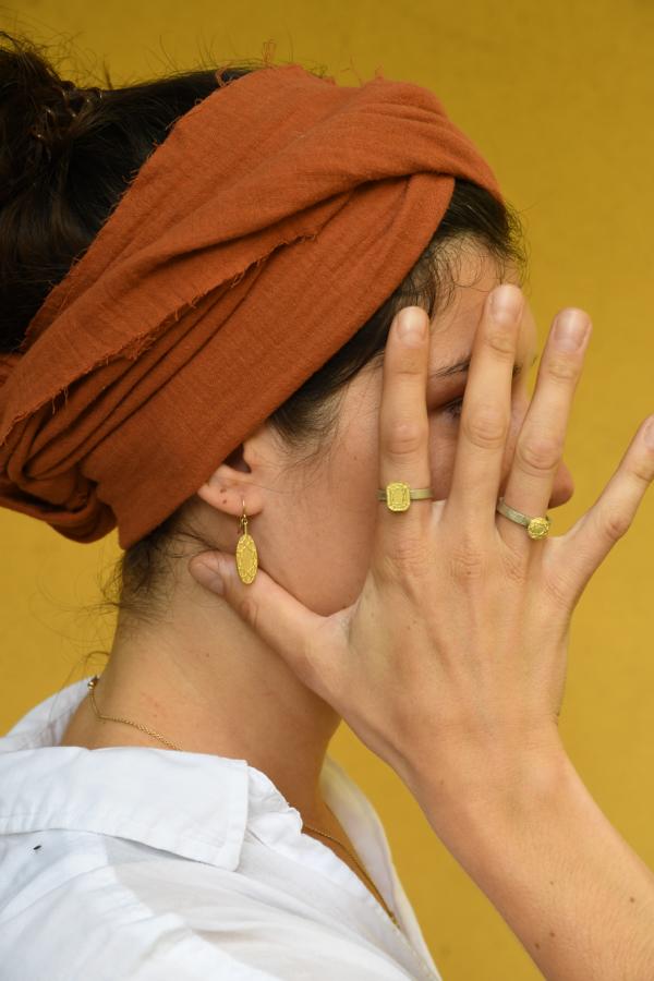 Frau mit orangenem Tuch im Haar trägt ausdrucksstarke Ringe aus Gold und Silber die gleichzeitig sehr fein gearbeitet sind