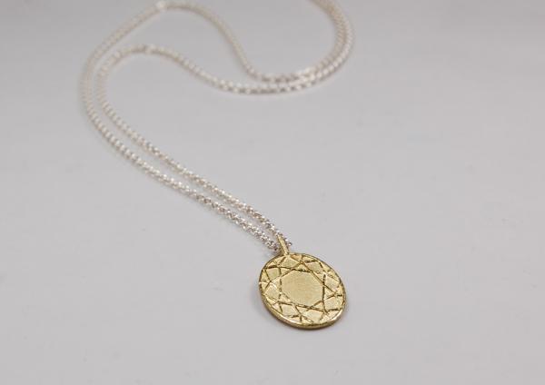 Ovaler Goldanhänger mit dem Ornament eines geschliffenen edelsteins