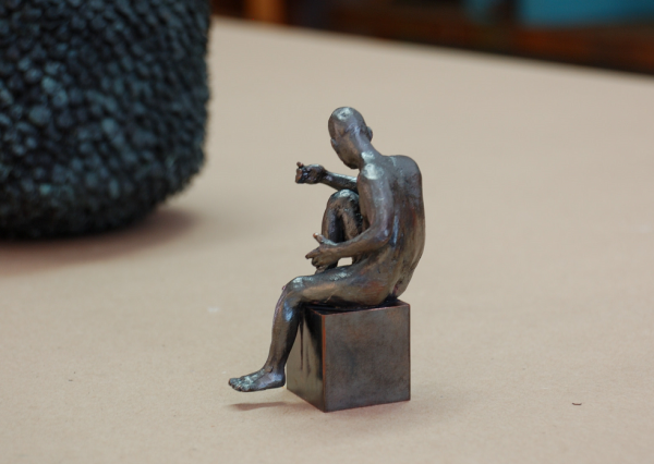 Bronzeakt, männlich, sitzend, im Begriff die Position zu ändern
