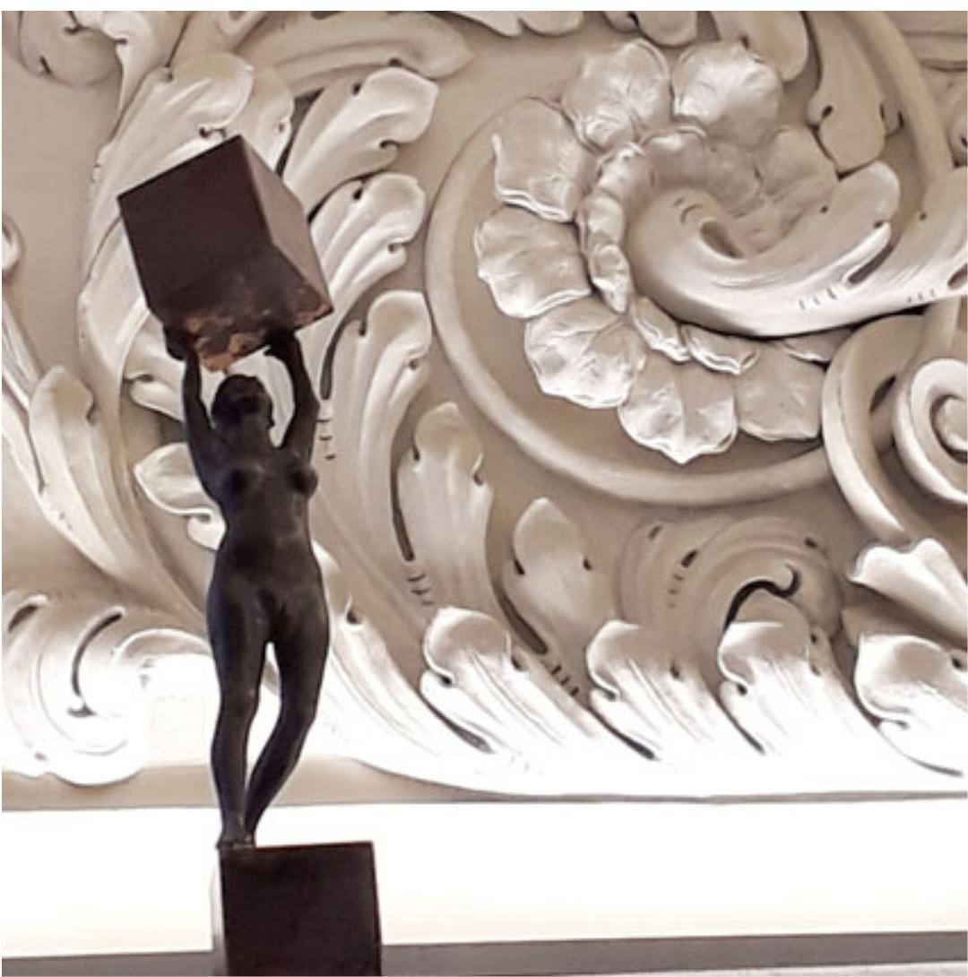 Figur von David Dott stemmt einen Kupferwürfel vor dem mächtigen Stuck im Fembo Haus Stadtmuseum Nürnberg