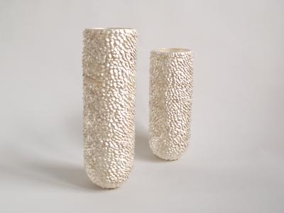 zwei zylindrische Gefäße aus Silber mit einer Oberfläche aus aus vielen kleinen Plättchen
