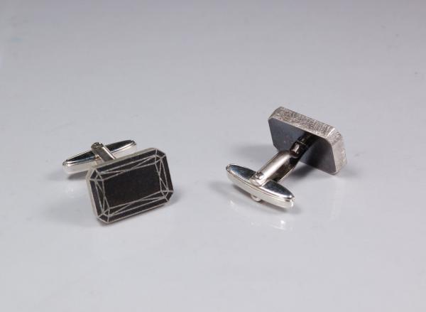 Die Manschetteknöpfe sind ganz aus Silber. Ihr hell-dunkel-Kontrast kommt durch die sogenannte Patinierung. Das ist eine Technik, mit der wir das Sterlingsilber gezielt dunkel oxidieren. Das Muster des Emerald Cut belassen wir dabei hell. Somit hebt sich die Zeichnung deutlich vom dunklen Untergrund ab. Und ein wichtiges Detail des strahlenden Edelsteins tritt akzentvoll zum Vorschein.