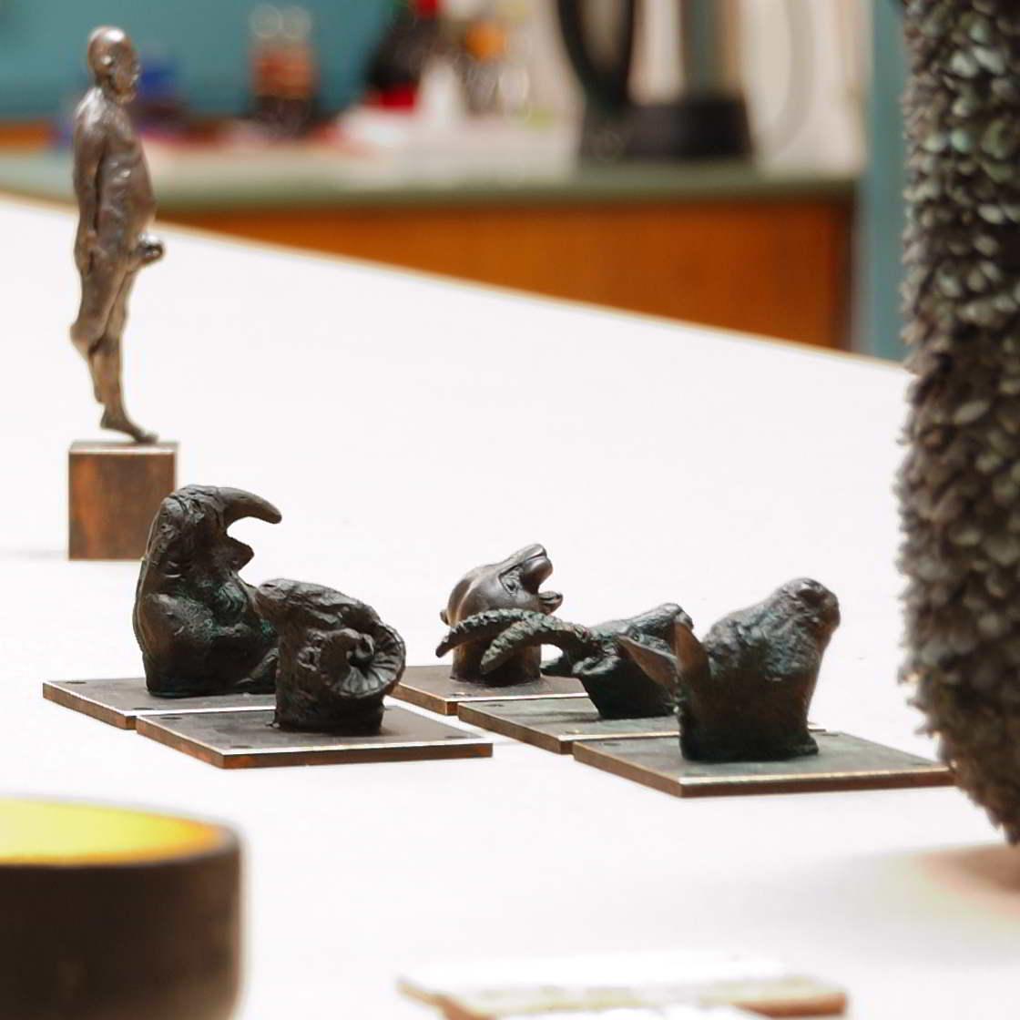 kleine Tierkopf Skulturen wie Widder, Nashorn, Esel, Steinbock und Jaguar. Im Hintergrund ist ein männlicher Akt in Bronze gegossen und auf einem Kupfersockel stehend zu sehen. Im Vordergrund ist ein Gefäß angeschnitten, dass eine sehr meditative Aura hat.