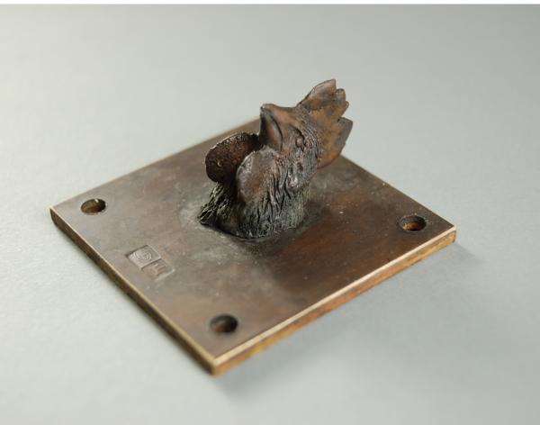 Welchen Charakter hat ein Huhn, das versucht David Dott in seiner kleinen Skulptur zu ergründen. Hühnerkopf auf 5 x 5 cm großer Platte, Materila Bronze